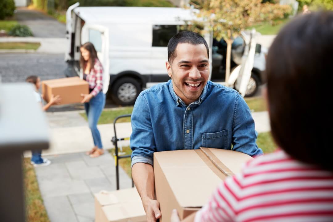 family smiling while moving boxes