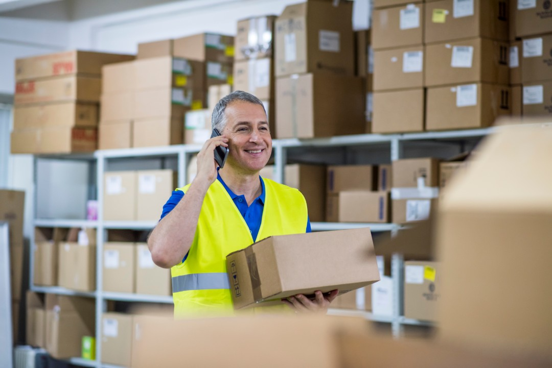 man on the phone smiling while holding box